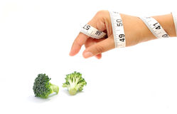 Diet. Tape measure wrapped around a hand reaching for broccoli Stock Images