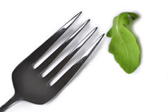 Diet. A fork  next to a rucola leaf to illustrate the concept of diets Stock Photography