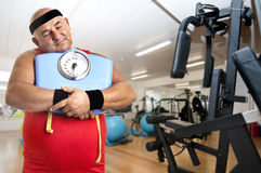 Diet. Large fitness man with weight scale in the gym Stock Image