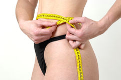 Diet. Young woman with tape measure controls if she has to make a diet Royalty Free Stock Image