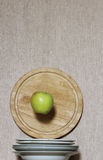 On diet. Green apple falling to the pile of plates Stock Photo