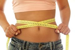 Diet. A woman belly with a measuring tape Stock Images