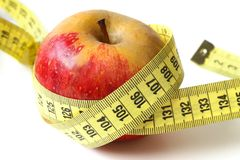 Diet. Apple wrapped up in a measuring tape Stock Image