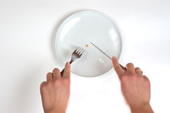 Diet. Female person is dieting with white empty plate Royalty Free Stock Image