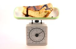 On diet. Weighing a piece of cheese cake Stock Photo
