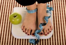 Diet. Woman foot on measuring scale with tape and apple Stock Images