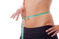 Diet. Close up view of woman measuring her waist on white back Royalty Free Stock Image