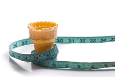 Diet. Concept image of a diet featuring a measuring tape around an empty ice cream cone, shot on white Stock Photography