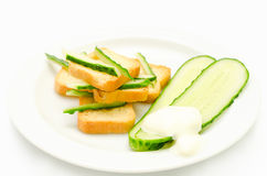 Diet appetizer of crispy toast and cucumber. Crunchy toasts on a plate with cucumbers and sauce stock photo