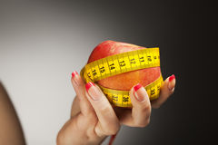 Diet apple with measure tape in woman hand Stock Photography