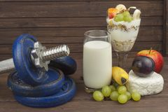 Diet for athletes build muscle mass. Protein snack. Dairy products and dumbbells. Stock Image