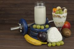 Diet for athletes build muscle mass. Protein snack. Dairy products and dumbbells. Fresh milk in the glass and muesli breakfast on a wooden table. Oatmeal with stock photography