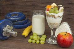 Diet for athletes build muscle mass. Protein snack. Dairy products and dumbbells. Royalty Free Stock Images