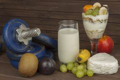 Diet for athletes build muscle mass. Protein snack. Dairy products and dumbbells. Royalty Free Stock Image