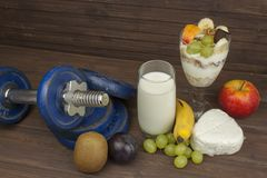Diet for athletes build muscle mass. Protein snack. Dairy products and dumbbells. Royalty Free Stock Photography