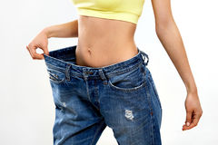 Diet. Beautiful Sporty Woman Showing How Much Weight She Lost. H Royalty Free Stock Photography