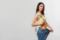 Diet. Beautiful Sporty Woman Showing How Much Weight She Lost. Stock Photo