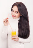 Diet. A beautiful young girl who follows the figure, drinking orange juice. The concept of healthy eating. White background. Royalty Free Stock Images