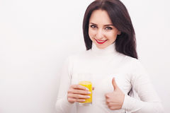 Diet. A beautiful young girl who follows the figure, drinking orange juice. The concept of healthy eating. White background. Stock Image