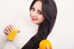 Diet. A beautiful young girl who follows the figure, drinking orange juice. The concept of healthy eating. White background. Royalty Free Stock Image