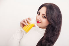 Diet. A beautiful young girl who follows the figure, drinking orange juice. The concept of healthy eating. White background. Stock Photo