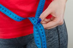 Woman measuring waist circumference with tape. Diet, being fit and healthy concept. Woman hand measuring waist circumference with tape stock image
