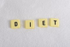 Diet block letters in crossword over sugar pile isolated on sweet grainy white sugar texture in dieting and healthy nutrition Stock Images