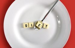 Diet block word in crossword with spoon on dish on table red mat taking one letter Stock Images