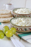 Diet breakfast: cottage cheese, crispbread and grapes. Diet breakfast: crispbread, green grapes and cottage cheese in ceramic ware hand-painted Stock Photo