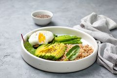 Diet breakfast with quinoa and vegetables. Healthy diet breakfast. quinoa, avocado, asparagus, poached egg  in a white ceramic plate on a gray stone background Royalty Free Stock Photography