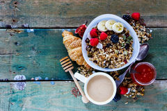 Diet breakfast set. Delicious breakfast composition. Bowl of organic muesli with banana, nuts, linseeds, fresh berries and figs, coffee, croissant, fruit jam Stock Image