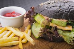 Diet burger with chicken, vegetables, and black bun. Restaurant food background Royalty Free Stock Images