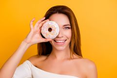 Diet, calories, healthcare, willpower, body care, concept, close. Up portrait of charming, cute girl with naked shoulders, holding sweet donut near eye Royalty Free Stock Photos