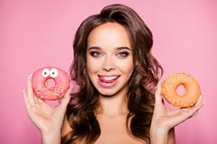 Diet, calories, healthcare, willpower, summer, body care, concep. T. Close up portrait of happy girl looking camera with donutes in arm and tounge out, so Royalty Free Stock Image