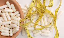 Diet capsules and measurement tape Royalty Free Stock Photography
