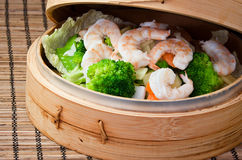 Diet chinese dish. Shrimp and broccolis steamed in bamboo steamer Stock Photography