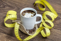 Diet coffee with cream in a white cup with tape measure Stock Photo