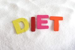 Diet color letters in crossword over sugar pile isolated on sweet grainy white sugar texture in dieting and healthy nutrition Royalty Free Stock Photo