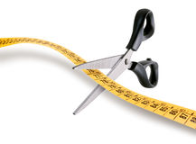 Diet concept. Scissors cutting a measuring tape over white background Stock Photos
