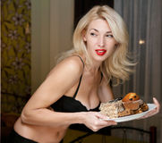 Diet concept. Young woman furtively at night regales cakes Stock Photography