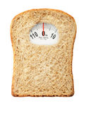 Diet concept. Weighing scales in form of a bread slice representing dietary warning royalty free stock image