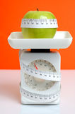 Diet concept. Green apple on a scale and measuring tape Royalty Free Stock Photos