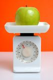 Diet concept. Green apple on a kitchen scale - diet concept Stock Image