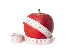 Diet Concept. A diet / dieting concept photo. Apple with a measure tape on royalty free stock image