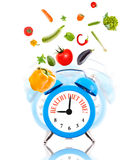 Diet concept, alarm clock ringing with vegetables. Stock Photos