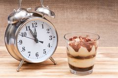 Diet concept with alarm clock: sweet Italian dessert tiramasu with delicate mascarpone cream from traditional recipe in glass stock image