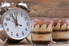 Diet concept with alarm clock: sweet Italian dessert tiramasu with delicate mascarpone cream from traditional recipe in glass royalty free stock images