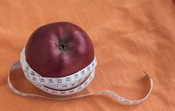Diet concept with Apple and measuring tape, on orange background with copy space.  royalty free stock photos