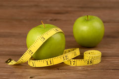 Diet concept,apple and measuring tape on wood background Royalty Free Stock Photos