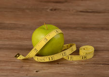 Diet concept,apple and measuring tape on wood background Stock Photos